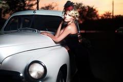 Forme a menina no estilo retro que levanta perto do carro velho imagens de stock royalty free