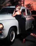 Forme a menina no estilo retro que levanta perto do carro velho fotografia de stock royalty free