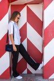 Forme a menina que levanta sobre o fundo listrado branco vermelho da parede A mulher da beleza com bordos cor-de-rosa prepara o l Fotografia de Stock