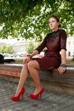 Forme a menina que senta-se no banco no parque urbano Foto de Stock