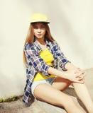 Forme a moça bonita que veste um tampão e uma camisa quadriculado imagem de stock royalty free