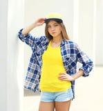 Forme a moça que veste um tampão e uma camisa quadriculado fotografia de stock royalty free