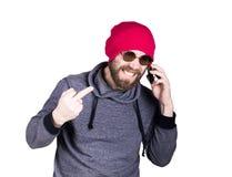 Forme a moderno o homem fresco nos óculos de sol e na roupa colorida, falando no telefone e expresse emoções diferentes foto de stock royalty free