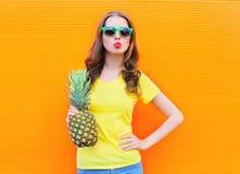 Forme a muchacha fresca en las gafas de sol con la piña sobre fondo colorido Imagen de archivo libre de regalías