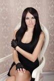 Forme a muchacha morena hermosa la presentación modelo en silla de lujo adentro Fotos de archivo