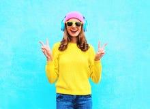 Forme a muchacha sonriente bastante fresca en auriculares que escucha la música las gafas de sol rosadas coloridas y el suéter de Imagen de archivo libre de regalías