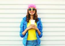 Forme a mujer bastante sonriente con la taza de café en ropa colorida sobre el fondo blanco las gafas de sol rosadas de un amaril Imágenes de archivo libres de regalías