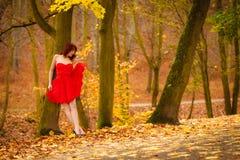Forme a mujer caminar de relajación del vestido rojo en parque Imagen de archivo libre de regalías