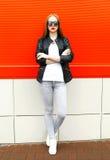 Forme a mulher à moda que veste um revestimento e óculos de sol do preto da rocha na cidade sobre o vermelho foto de stock
