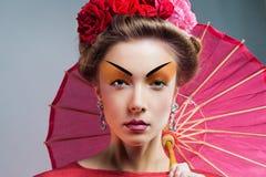 Forme a mulher asiática que veste o quimono vermelho japonês tradicional foto de stock