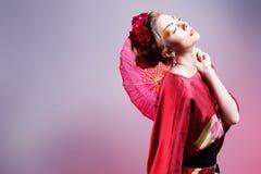 Forme a mulher asiática que veste o quimono vermelho japonês tradicional. Gei Fotos de Stock