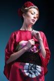 Forme a mulher asiática que veste o quimono vermelho japonês tradicional. Gei Fotografia de Stock Royalty Free