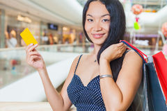 Forme a mulher asiática que guarda o cartão de crédito e os sacos, shopping Fotos de Stock Royalty Free