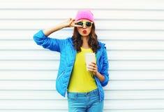 Forme a mulher bonita com o copo de café na roupa colorida sobre o fundo branco que veste o casaco azul cor-de-rosa dos óculos de Fotos de Stock Royalty Free