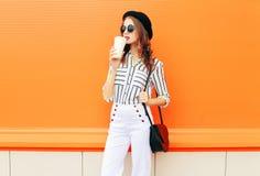 Forme a mulher bonita com o copo de café que veste uma embreagem da bolsa das calças do branco do chapéu negro sobre a laranja co imagens de stock