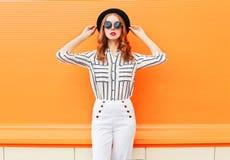 Forme a mulher bonita os óculos de sol vestindo modelo do chapéu negro as calças brancas sobre a laranja colorida Imagem de Stock