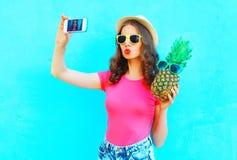 Forme a mulher bonita que toma o autorretrato da imagem no smartphone com o chapéu de palha vestindo do abacaxi sobre o azul colo Imagem de Stock Royalty Free