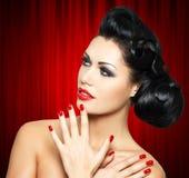 Forme a mulher com bordos vermelhos, pregos e penteado criativo Imagem de Stock