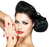 Forme a mulher com bordos vermelhos, pregos e penteado criativo Imagem de Stock Royalty Free