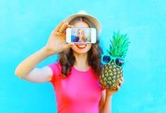 Forme a mulher com o abacaxi que toma o autorretrato da imagem no smartphone sobre a tela azul colorida do fundo Imagens de Stock