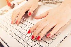 Forme a mulher com os pregos lustrados vermelhos que trabalham no portátil Escrita fotografia de stock