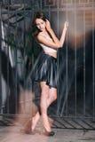 Forme a mulher com pés longos em sapatas pretas do salto alto e na saia de couro curto Fotos de Stock Royalty Free