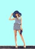 Forme a mulher loura bonita que veste o vestido listrado, chapéu de palha Imagens de Stock