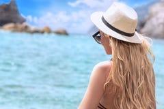 Forme a mulher no chapéu do verão que relaxa na praia imagens de stock