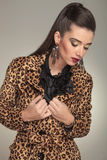 Forme a mulher que fixa seu colar ao olhar para baixo Foto de Stock