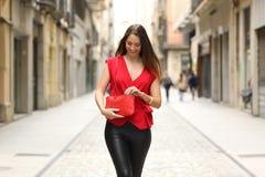 Forme a mulher que procura em no seu saco e passeio Imagem de Stock