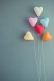 Forme multicolore de coeur de ballons sur le fond bleu de mur Image stock
