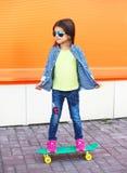 Forme a niño con llevar del monopatín las gafas de sol y la camisa a cuadros Fotografía de archivo libre de regalías