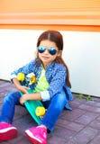 Forme a niño con llevar del monopatín las gafas de sol y la camisa a cuadros sobre fondo anaranjado Imagen de archivo