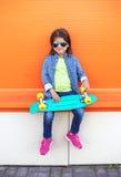 Forme a niño con llevar del monopatín las gafas de sol y la camisa a cuadros sobre naranja Fotografía de archivo libre de regalías