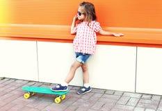 Forme a niño de la niña con llevar del monopatín las gafas de sol en ciudad Imagenes de archivo