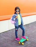 Forme a niño de la niña con llevar del monopatín las gafas de sol y camisa a cuadros y mochila sobre naranja Fotos de archivo