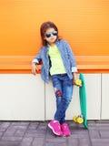 Forme a niño de la niña con llevar del monopatín las gafas de sol y la camisa a cuadros sobre naranja Fotografía de archivo