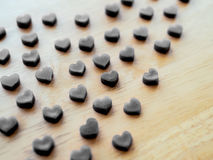 Forme noire de coeur faite à partir de la bougie sur la table en bois Images stock