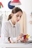Forme o blogger da mulher em um espaço de trabalho criativo que escolhe cores. fotos de stock