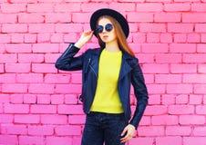 Forme o chapéu negro vestindo da mulher e o revestimento feito malha amarelo da camiseta sobre tijolos cor-de-rosa coloridos Foto de Stock Royalty Free