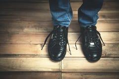 Forme o homem na sapatilha preta com calças de ganga no assoalho de madeira Fotografia de Stock Royalty Free