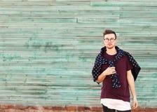 Forme o indivíduo em poses dos vidros perto de uma parede de madeira no azul Imagens de Stock Royalty Free