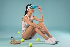 Forme o modelo fêmea moreno que senta-se com raquete de tênis fotos de stock royalty free