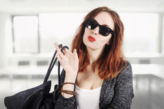 Forme o modelo na moda novo na roupa agradável que levanta no estúdio Óculos de sol e bolsa vestindo no fundo do escritório do lo Imagens de Stock