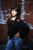 Forme o retrato da mulher nova com uma parede de tijolo Fotografia de Stock Royalty Free