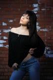 Forme o retrato da mulher nova com uma parede de tijolo Fotografia de Stock