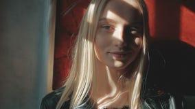 Forme o retrato de uma jovem mulher bonita com olhos azuis e cabelo louro em um casaco de cabedal interno vídeos de arquivo