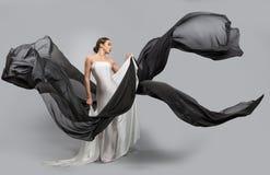 Forme o retrato de uma mulher bonita em um vestido branco e preto A tela voa no vento imagem de stock