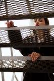 Forme o retrato exterior da mulher à moda na rua, nas escadas do metal com vista na cidade Imagem de Stock Royalty Free