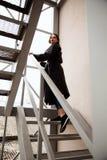 Forme o retrato exterior da mulher à moda na rua, nas escadas do metal com vista na cidade Fotos de Stock Royalty Free